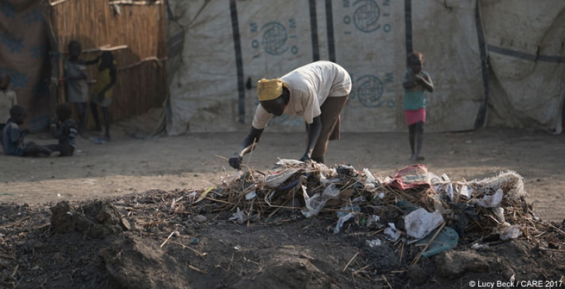 A woman cleans up garbage in Bentiu Protection of Civilians site in Unity State, South Sudan