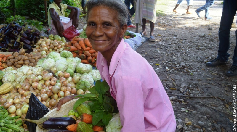 Marie Melia in Haiti with a basket of fresh vegetables she purchased with Kore Lavi vouchers.