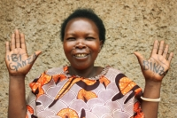 Ammpmcoata shows off her 'Powerful Hands' (Ibuganza Birakiza in Kirwanda). She is a CARE VSLA member since 2007, in the village of Akagarama in Rwanda