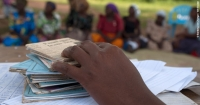 A pile of savings books sit on a table as members of a village savings group meet in Bugiri, Eastern Uganda