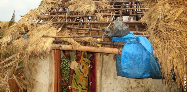 Women take stock of the damage done to their home by the cyclone that struck Odisha in October 2013