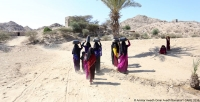 Women in Lahj, Yemen, carrying water they collected from a CARE water point