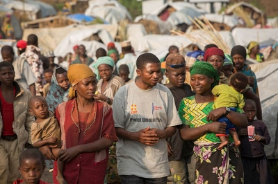 CARE DRC Food Security Manager, Joseph Kakuru, talks with displaced people in Rubaya Camp, DRC. © CARE / Jake Lyell 2013