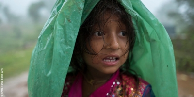 A girl sheltering from monsoon rains in Dhading District, Nepal, in a community where many were still living in temporary shelters after the 2015 earthquakes
