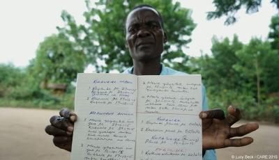 Ibrahim, a farmer in Malawi, with the rainfall record he keeps for his farmers committee