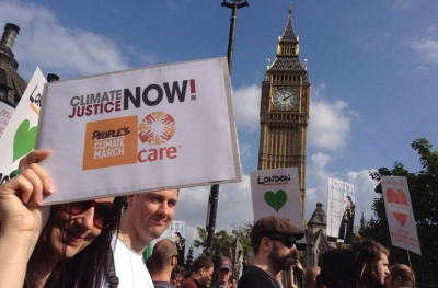 Catherine Pettengell holding a placard as the marchers pass Big Ben in London