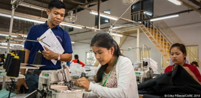 Line leader Maly Thorn is supervised by her Production Manager at a garment factory in Phnom Penh, Cambodia