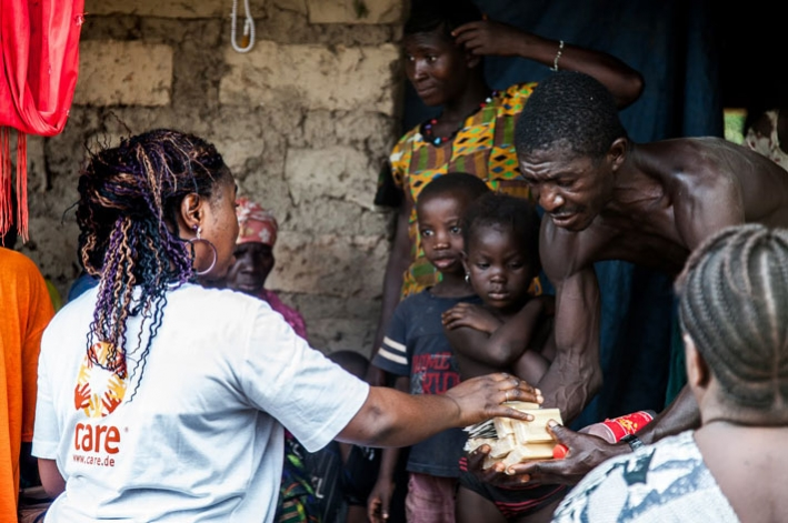 CARE staff explain anti cholera tools to a family in Sierra Leone. © CARE / Tim Freccia