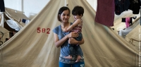 Berivan, from Aleppo, Syria, with her daughter in front of her tent in Vasilika refugee camp, Greece