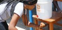 Danica Casimir washes her hands during hygiene kit distribution in Haiti.