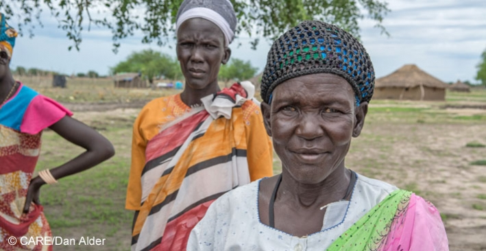 Aluat Deng Gach, widow and mother of 7, arriving at a meeting about a CARE livelihoods project in her village in Jonglei State