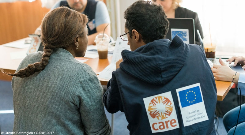 A woman refugee talking to a CARE staff member at an ECHO-funded advice and information project in Greece