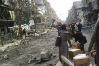 Women with United Nations Relief and Works Agency (UNRWA) aid packages in the besieged Palestinian refugee camp of Yarmouk in Damascus (photo taken on a mobile phone)