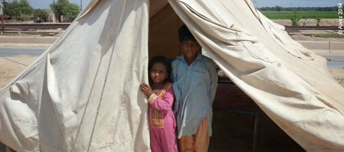 Children look out from a temporary tent home after flooding caused by heavy rains in September 2014 affected more than 2 million people. Photo from CARE partner organisation Awaz.
