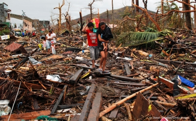 Survivors pass through an area devastaed by Typhoon Haiyan on November 12, 2013 in Leyte, Philippines.