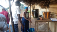 Liberia: A woman washes her hands at a CARE handwashing station before going shopping