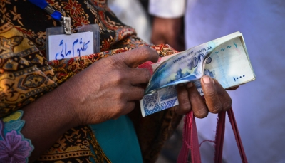 A female road maintenance worker in Pakistan counting her salary during a cash distribution at a mobile service vehicle of Tameer Bank