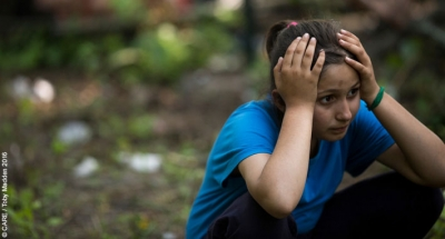 A girl holds her head at a refugee camp in Serbia, July 2016 (note: image for illustrative purposes, not necessarily an unaccompanied minor)