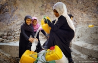 Girls pour clean water from the well in Lahj, Yemen, into their cans