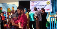 People waiting outside a mobile health clinic set up by CARE and local partner organisation Palestinian Medical Relief Society (PMRS) at a primary school in Gaza city, August 2014