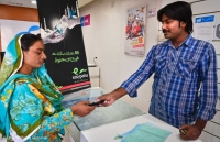 A woman receiving payment for her work through the Easypaisa mobile banking system