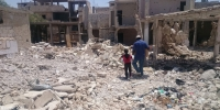 A man and boy carrying emergency shelter materials across bombed out rubble in southern Syria (2016)