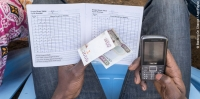 A mobile transaction during a savings group meeting in Kenya