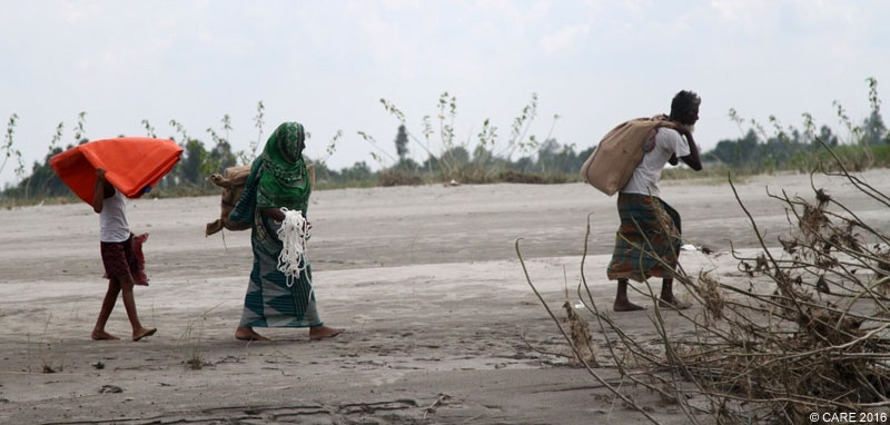 A family in Bangladesh carrying emergency aid after floods in 2016