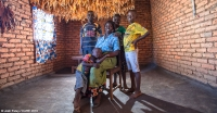Makulata, a member of the local VSLA, with her family in their home in Lilongwe District, Malawi.
