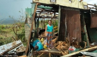A woman stands in her devastated home after Typhoon Haiyan hit Merida village in the Philippines, November 2013