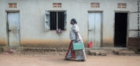 A member of the Village Savings and Loan Association in Kawete, Uganda, carrying the savings box