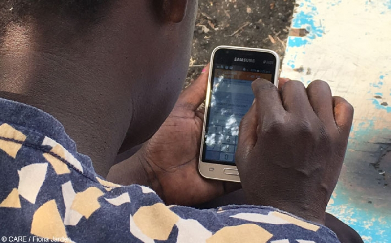 CARE VSLA member in rural western Kenya making a transaction using the Kenya Equitel mobile app