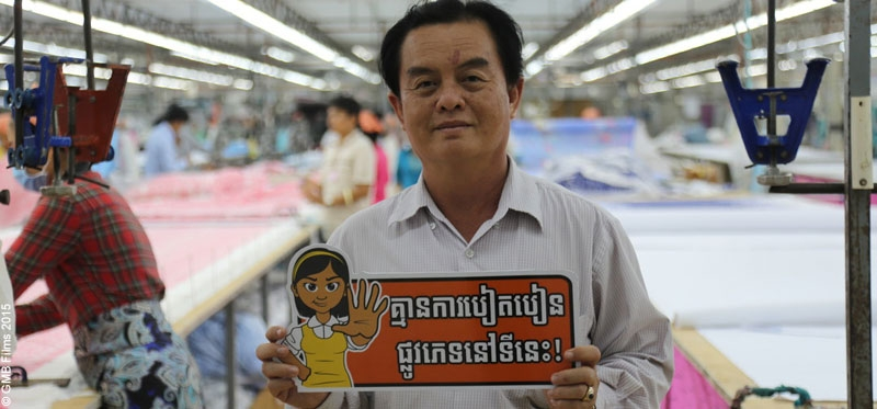 A garment factory manager holds a sign supporting CARE Cambodia's campaign against sexual harassment in the workplace