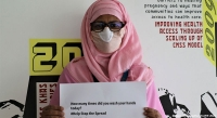 Mansura Begum, who works for CARE Bangladesh, displays a COVID-19 awareness message