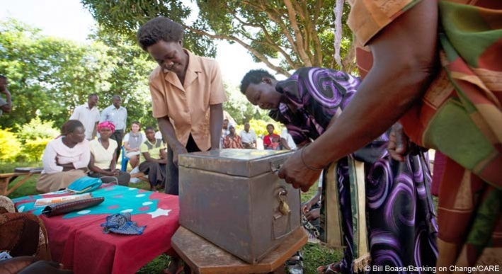 Members of the Yesu Amala VSLA group open the group's shared safe during a meeting of the group's members in Busia District, Eastern Uganda